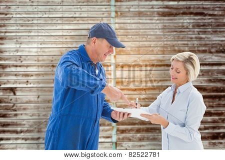 Happy delivery man with customer against wooden planks