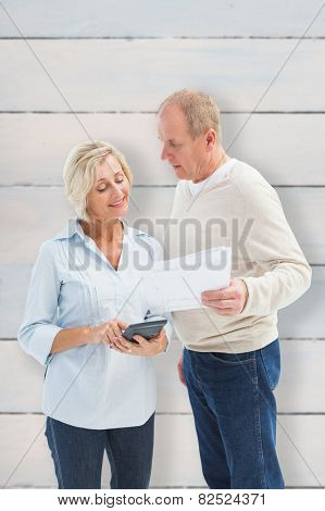 Mature couple working out their bills against wooden planks