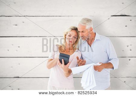 Anxious couple working out their bills against white wood