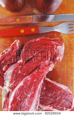 fresh raw beef steak entrecote fillet ready to prepare on cut board with cutlery and castor isolated over white background