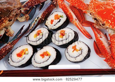 Japanese Traditional Cuisine - California Roll with Avocado and Salmon, Cream Cheese . on black dish with red and blue crabs .
