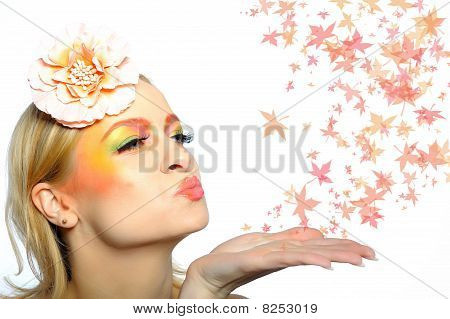 Concept Of Autumn Fashion Woman With Creative Eye Make-up Blowing Autumn Leafs From Her Hand