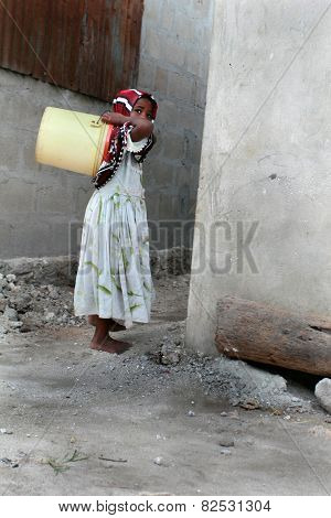 Little Muslim Girl Is Empty Yellow Plastic Bucket, Zanzibar, Fishing Village.