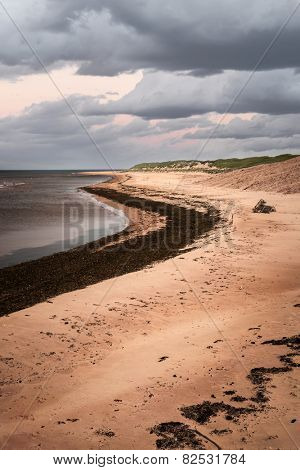 Beach at sunset in Prince Edward Island, Canada with dark cloudy sky