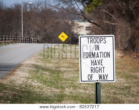 A metal sign that says Troops In Formation Have Right Of Way along the side of a road.