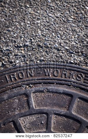 Close up of a metal manhole cover with the words Iron Works.