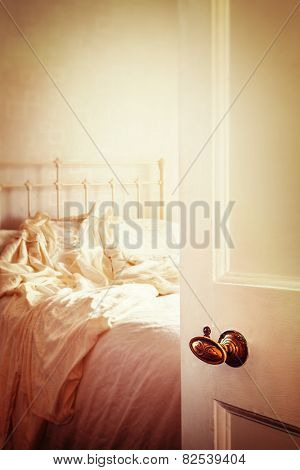 Open bedroom door with wedding dress lying on the bed