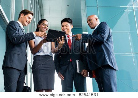 Pan Asian and Caucasian business team looking at tablet computer watching presentation of new project