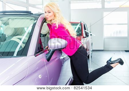 Woman choosing car for buying in dealership really desiring and kissing the auto