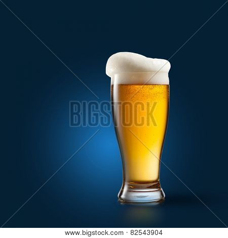 Beer in glass on blue background