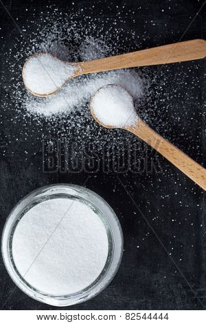 sugar in wooden spoons and glass jar on black background