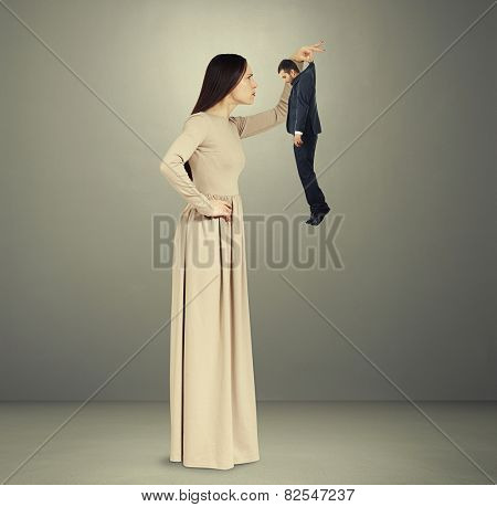 beautiful young woman scrutinizing small man in black suit over grey background