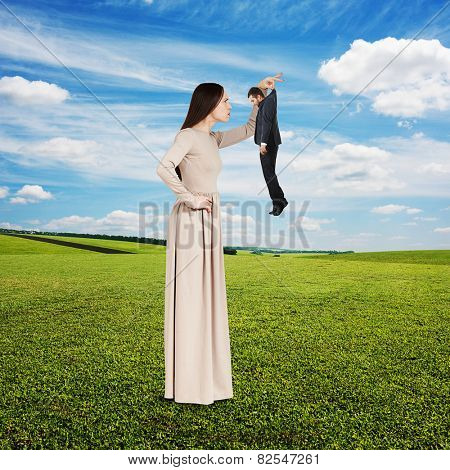 young serious woman looking at small man. photo at outdoor