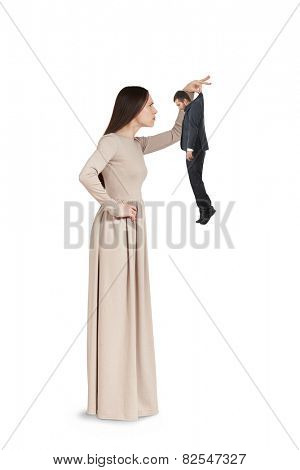 strict young woman to examining small man. isolated on white background