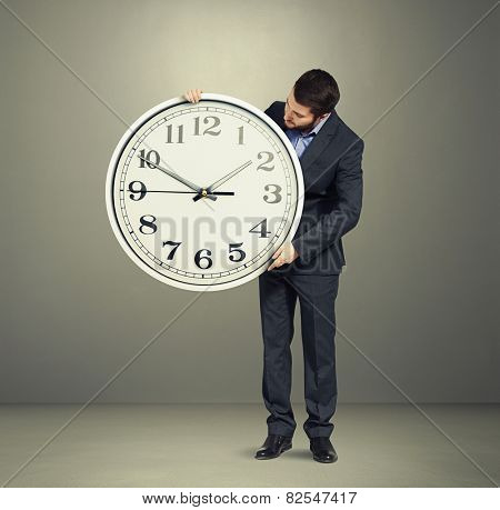 businessman holding big white clock and looking at clock dial over grey background