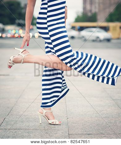 Legs Of Woman With High Heels Dressed Long Striped Dress