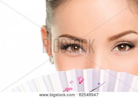 Asian beauty eyes - makeup woman looking with oriental fan. Mysterious chinese lady showing eyeliner and mascara hiding face behind accessory.