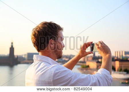 Tourist taking photograph of sunset in Stockholm skyline and Gamla Stan. Man photographer taking photos using smartphone camera. Male traveler sightseeing visiting landmarks in Sweden, Scandinavia.