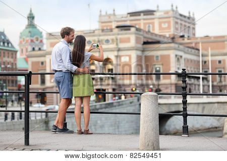 Couple taking smartphone photos in Stockholm city. Young adults tourists walking in the city of Stockholm during summer and taking selfies or pictures of the town.