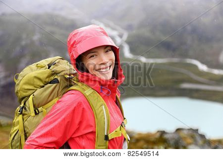 Hiker woman hiking with backpack in rain on trek living healthy life. Smiling fresh and candid young asian girl walking on hike in mountain nature landscape while raining in Swiss alps, Switzerland.