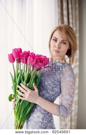 Happy woman with a bouquet of pink tulips.