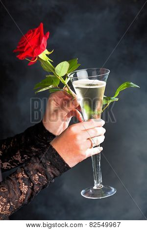 a young woman in evening dress with a red rose and a glass of sparkling wine or champagne. photo icon for valentine's day, romance and wedding day