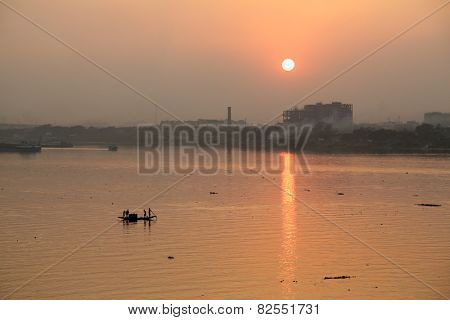 KOLKATA, INDIA - FEB 08: A boat crossing the river Ganges (aka River Hoogly) during sunset on February 08, 2014