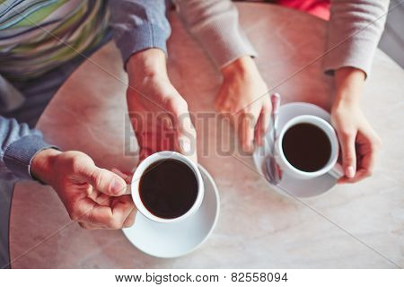 Porcelain cups with hot arabica held by young couple