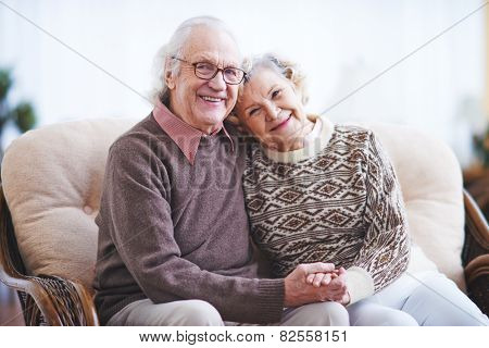 Affectionate couple in casualwear having rest at home