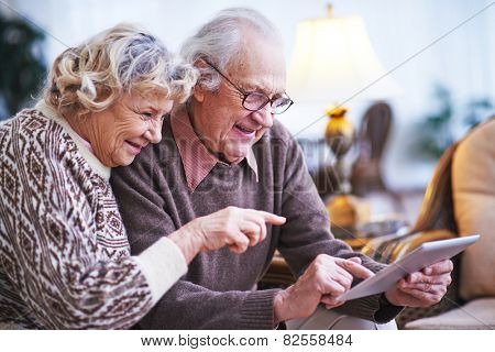 Elderly husband and wife with touchpad networking at leisure