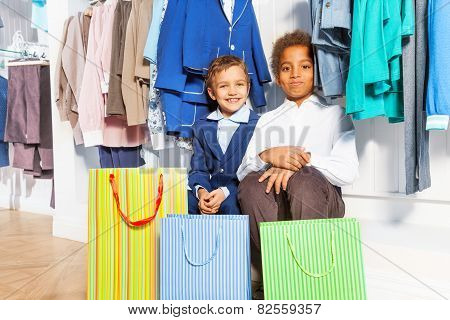 Two boys sitting under hangers with clothes