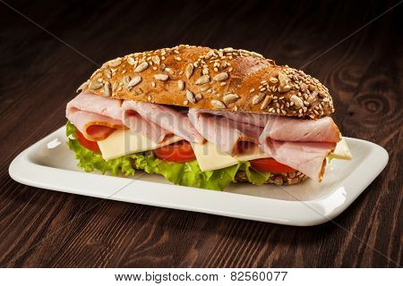 Ham sandwich with lettuce, cheese, tomato on plate on wooden table