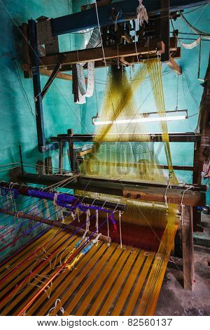 Man weaving silk sari on loom. in Kanchipuram, Tamil Nadu, India. Kanchipuram is famous for hand woven silk sarees and most of the city's workforce is involved in  weaving industry