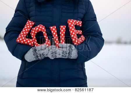 Girl In Blue Down Jacket And Gloves Holding A Sign