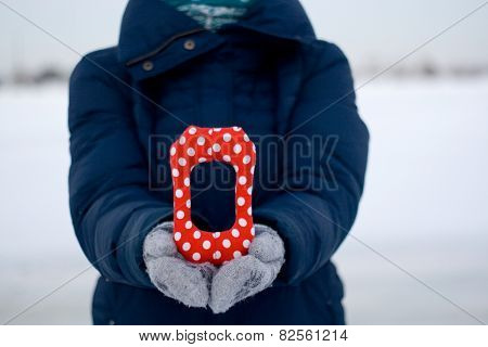 Girl In Blue Down Jacket And Gloves Holding A Letter Of Tissue