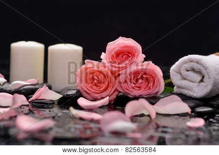 three rose and towel with candle on therapy stones