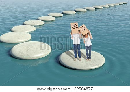 Mature couple wearing boxes over their heads against zen rock pool