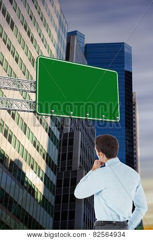Thoughtful businessman with hand on chin against low angle view of skyscrapers