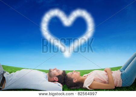 Attractive young couple lying down against green field under blue sky