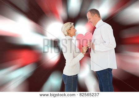 Older affectionate couple holding pink heart shape against digitally generated twinkling light design