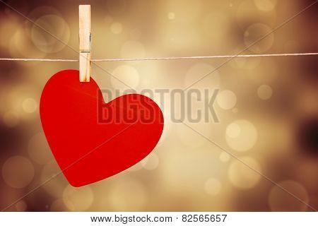 Heart hanging on line against orange abstract light spot design