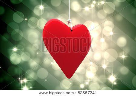 Red heart against light design shimmering on green