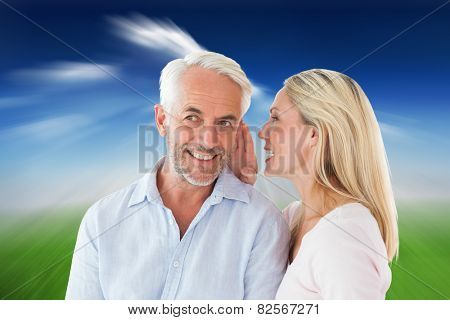 Woman whispering a secret to husband against blue sky over city