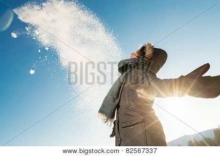Happy woman posing against high snowy mountains
