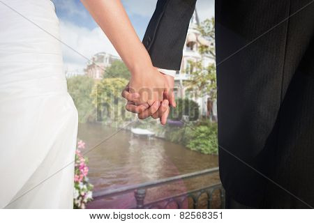 Close up of cute young newlyweds holding their hands against canal in amsterdam