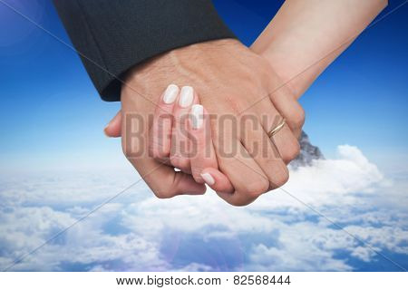 Newlyweds holding hands close up against mountain peak through the clouds