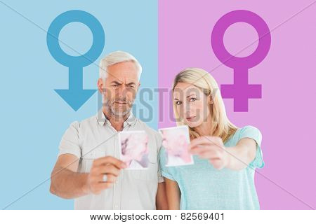 Unhappy couple holding two halves of torn photograph against pink and blue