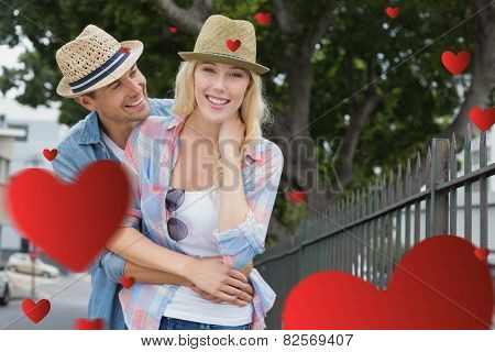 Hip young couple smiling at camera by railings against hearts