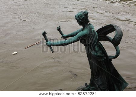 PRAGUE, CZECH REPUBLIC - JUNE 3, 2013: Art Nouveau bronze statue of a torchbearer at the Svatopluk Cech Bridge partially flooded by the swollen Vltava River in Prague, Czech Republic.