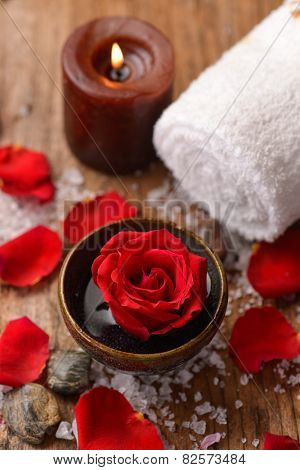 rose in bowl with pile of salt ,stones ,candle,towel on old wooden board